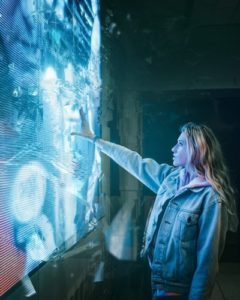 teenager touching a wide aquarium glass wall with creatures within