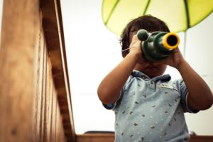 photo of a young child looking through a telescope