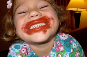 photo of young girl smiling with lipstick painted all over her mouth