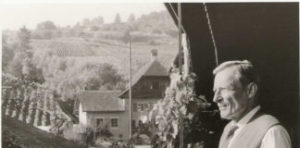 Black and white photo of Jean Gebser with vineyard in the background