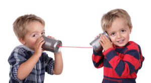 Photo of two young boys talking to each other through a string and tin cans