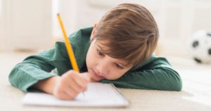 photo of a child doing his homework (and not seeming to like it)