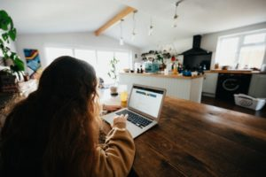 Picture of back of girl working on computer in the kitchen of her home