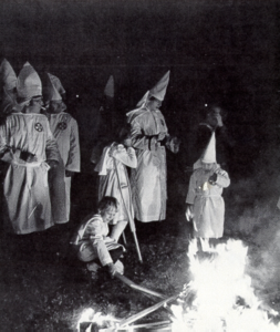 black and white photo of a Ku Klux Klan rally with people (including kids) in white sheets and hoods