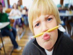 color photo of child in school with pencil held between his lips and nose