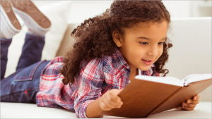 color photo of young girl laying on stomach reading a book