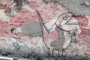 color photo of child pointing a long stick at the large drawn image of a monster on a brick wall