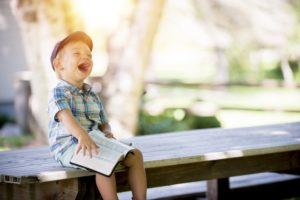 Color photo of a boy sitting on an outdoor bench laughing with a book in his lap.