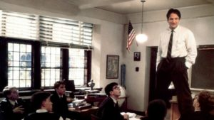 color photo of Robin Williams standing on desk in classroom in film Dead Poet's Society