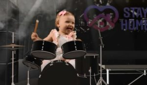 color photo of a young girl playing a drum set