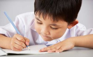 color photo of a young child writing with a blue pencil