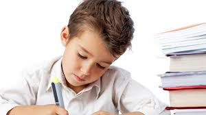 color photo of young boy writing with books at his side