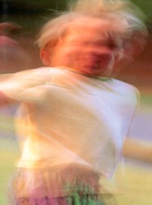 A color photo showing a blurred image of a child in the act of moving around